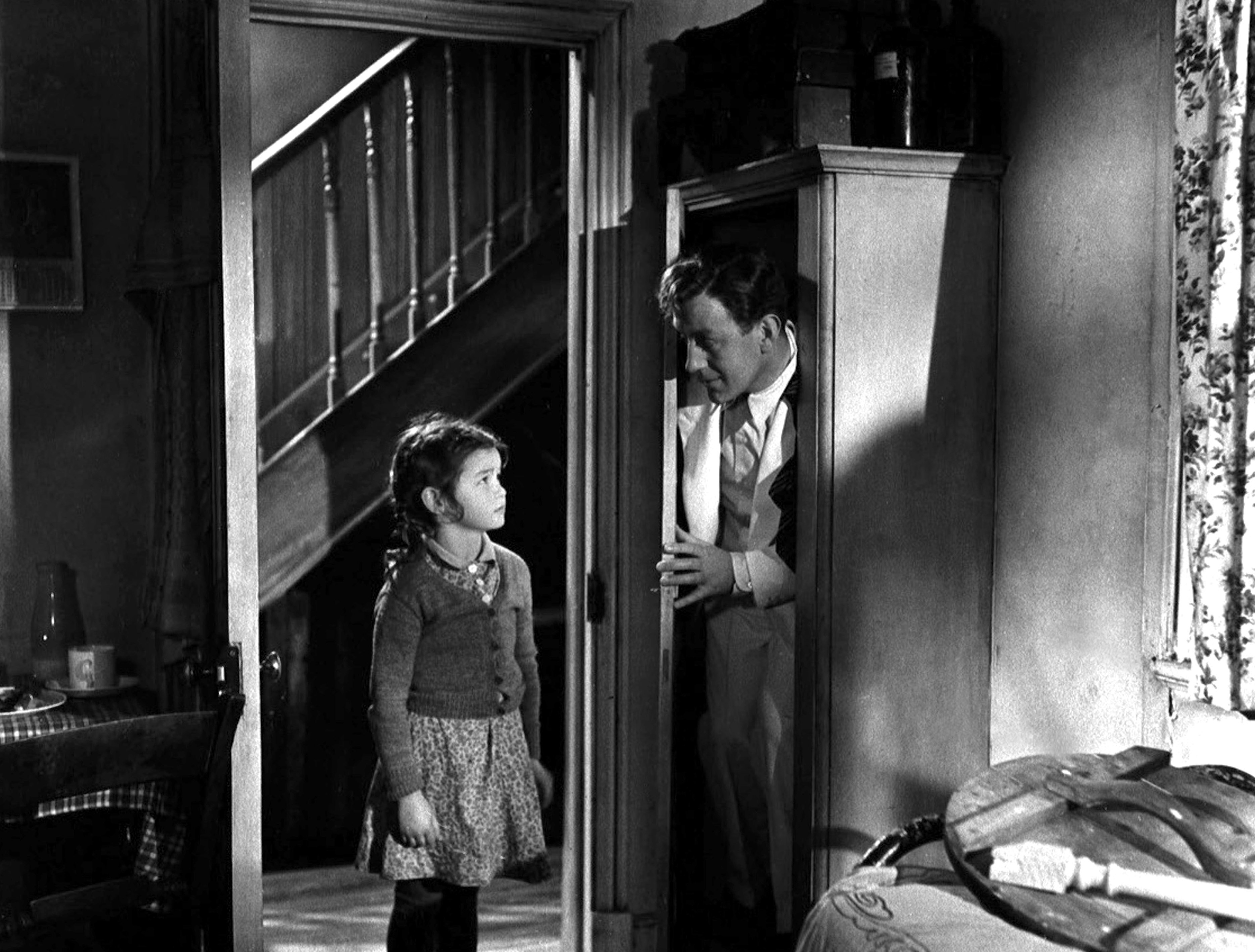 Alec Guiness hiding in a wardrobe from a young girl (from the movie, The Man in the White Suit)